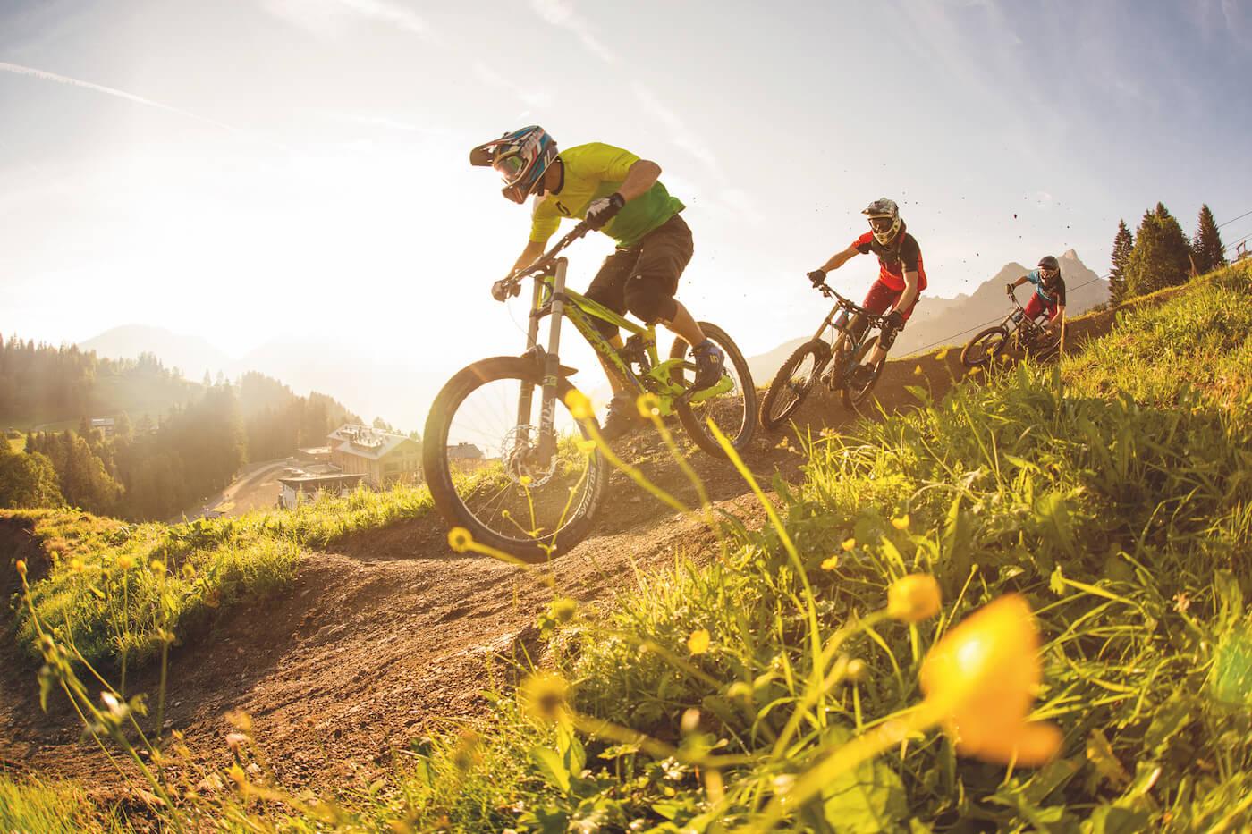 Drei Mountainbiker beim Downhillfahren vor Bergkulisse