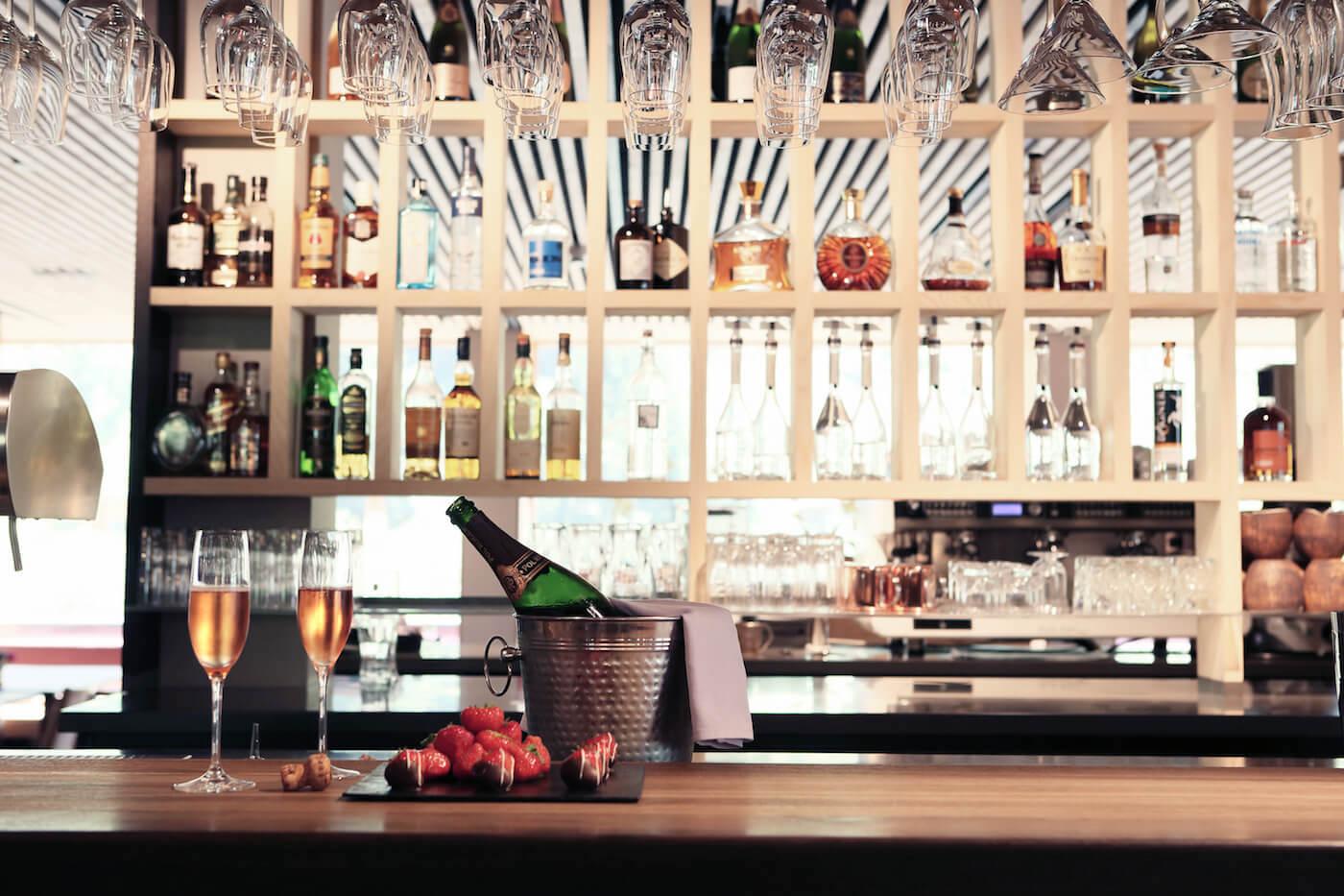 Bar mit einer geöffneten flasche champagner auf dem tresen und zwei gefüllten gläsern