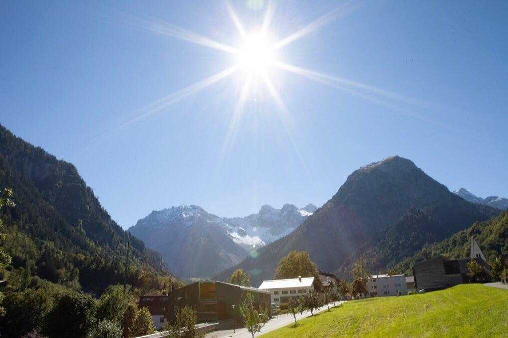 Brandnertal mit grüner wiese, strahlender Sonne und Alpen im Hintergrund
