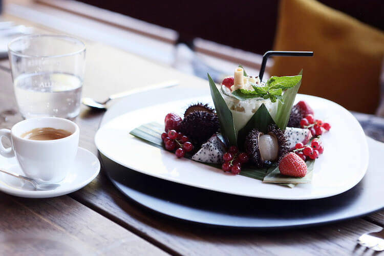 Tasse Cafe und angerichtete Süssspeise auf einem weissen Teller